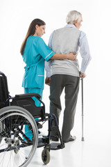 Senior care. Confident nurse helping senior men to walk while is