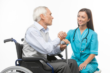 Senior care. Cheerful young nurse holding senior man hand and sm