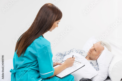 Taking care of seniors. Confident young nurse sitting near the p