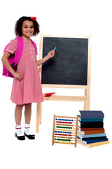 Pretty schoolgirl pointing at chalkboard
