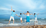 Mother and three sons are jumping on beach
