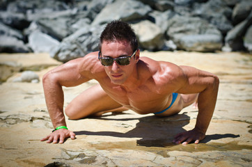 Attractive young muscle man posing on yellow rock under the sun