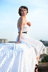 Beautiful young woman posing on the roof building.