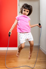 Little girl jumping rope at home