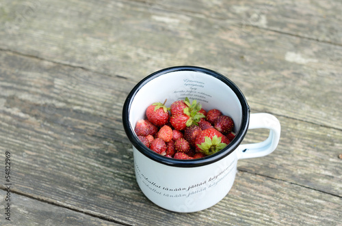 Wild strawberry in metal cup on wooden table