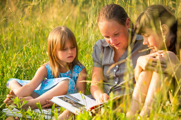 Portrait of three cute little girls reading book.