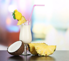 Pina colada drink in cocktail glass, on bright background