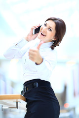 Cheerful businesswoman on phone and showing tumbs up
