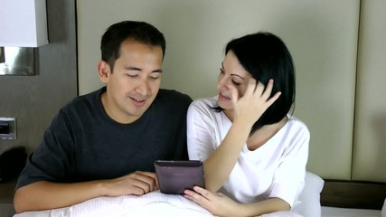 happy couple sitting on bed and looking at the tablet pc