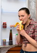 Girl eats banana near the refrigerator
