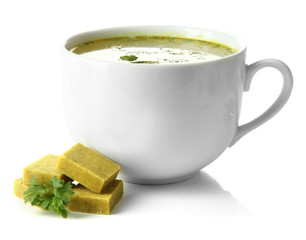 Cup of soup with bouillon cubes, isolated on white