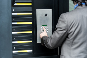 Man entering security code to unlock the door