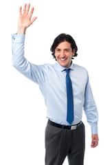 Businessman waving hi to his colleague