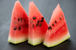 Segments of juicy watermelon on black wooden background