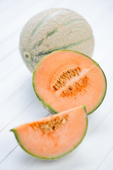 Rockmelons: one whole and one cut, vertical shot