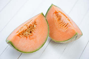 Two slices of cantaloupe melon on white wooden boards