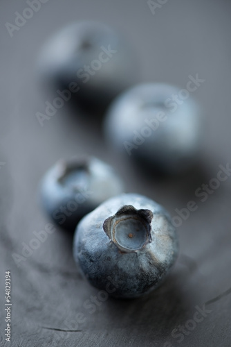 Vertical shot of blueberries on wooden boards, shallow DOF