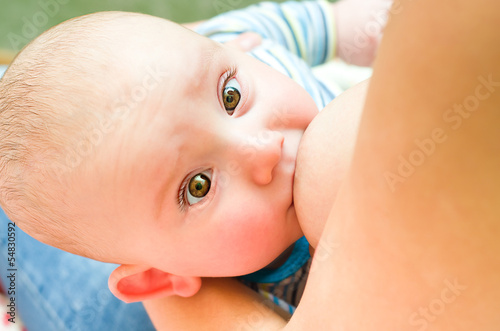 Baby is fed mother's milk looking at camera