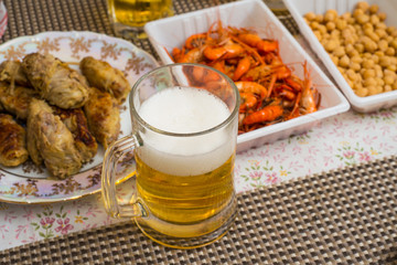 Beer, shrimp, pea, and other appetizers on a table