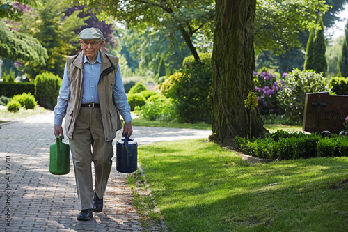 Aged man carries watering cans on a cemetery