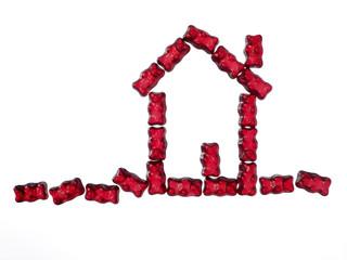 rote Gummibaerchen in Hausform auf weissem Hintergrund