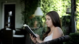 Beautiful woman reading book on veranda