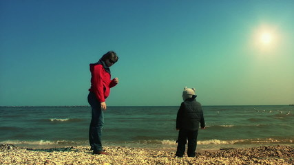 Mother teaching her son to throw sea shells