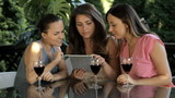 Pretty women with tablet, drinking wine