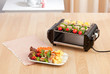electric grill stove with barbecue display on wooden table