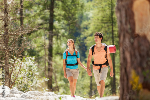 Couple is walking through the woods while smiling