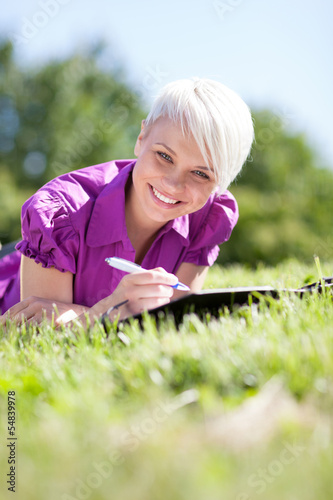 Beautiful female student is studying in a green field