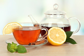 Cup of tea with lemon on table on light background