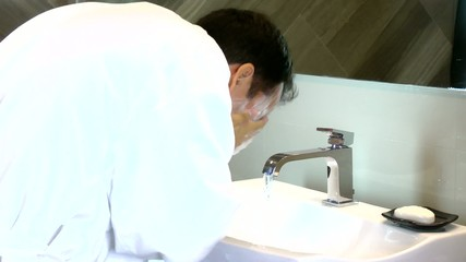 Young man washing his face in sink