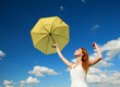 Girl with umbrella at sky background.