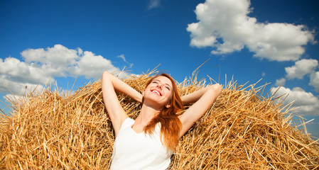 Redhead girl lying down on hay