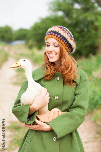 Redhead girl with duck at outdoor.