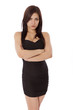 Young woman in a little black dress pouts with arms crossed.