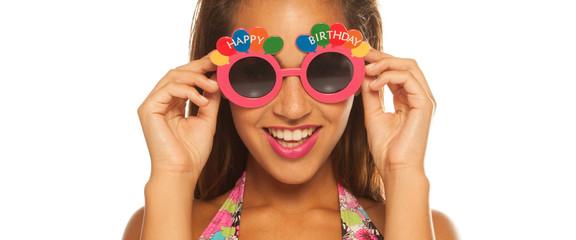 bautiful girl celebrating wearing birthday sunglasses on white