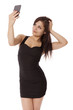 Young woman in a little black dress takes a selfie with her cell