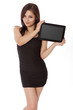 Pretty woman in a little black dress holds a blank tablet comput