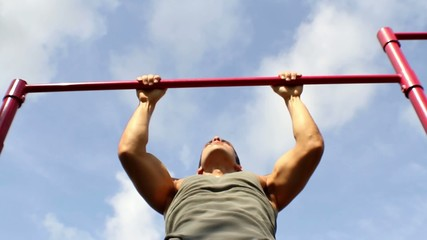 Athlete pulls on the bar. Pull ups