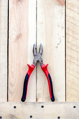 red pliers tool on a brown wooden background