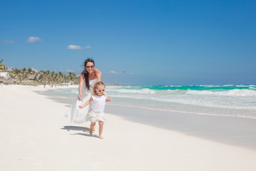Young beautiful mother and her adorable little daughter running