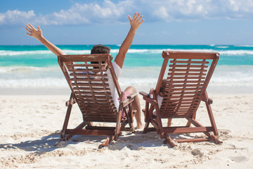 young father with daughter in beach chairs raised their hands up