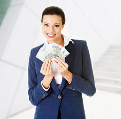 Happy woman holding euro money