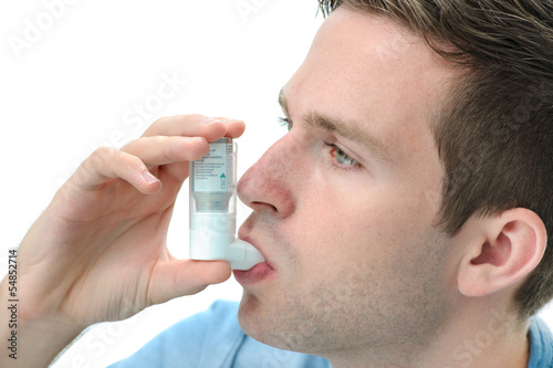 Young man using an asthma inhaler