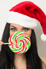 Pretty woman with santa hat holding lollipop over mouth