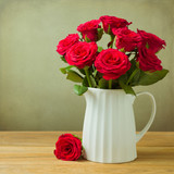 Rose flower bouquet in jug on wooden table
