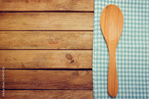 Wooden spoon and tablecloth over wooden background
