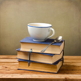 Old books and cup of coffee on wooden table